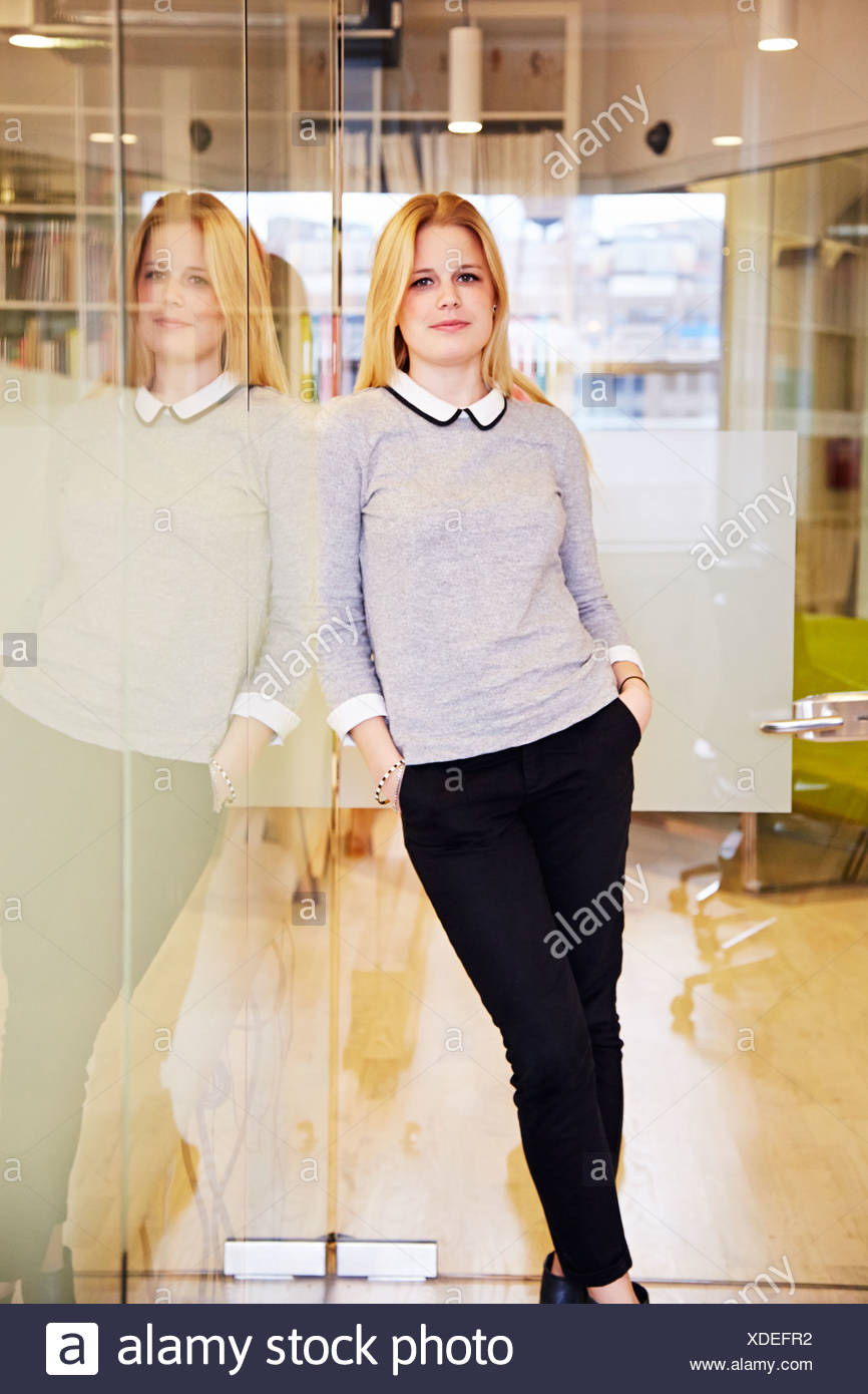Female office worker leaning against glass - Stock Image