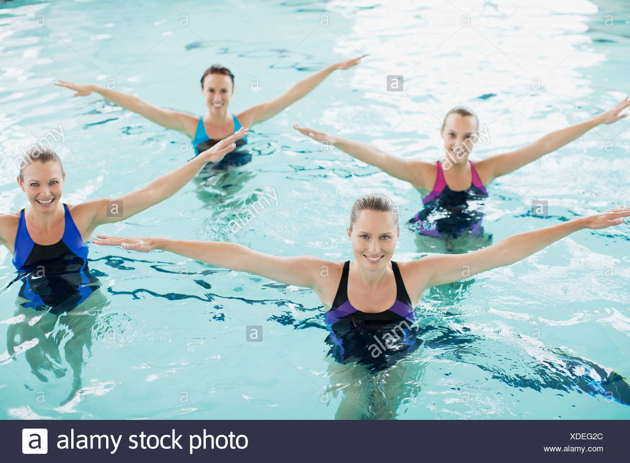 Portrait of smiling synchronized swimming team in swimming pool - Stock Image