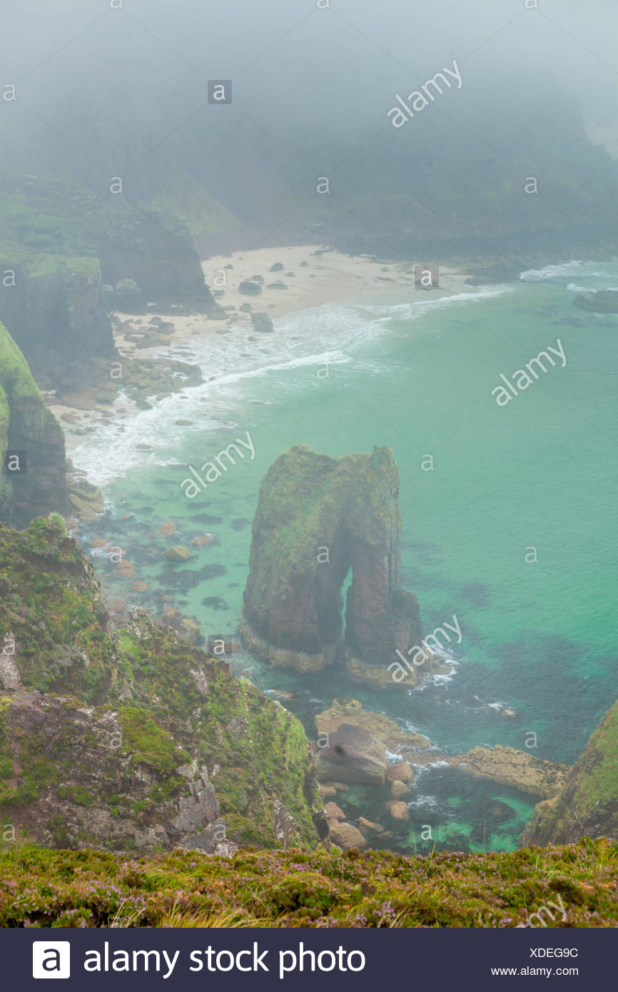 rock arch in the blue sea below the cliffs of Wester Ross, Scotland - Stock Image