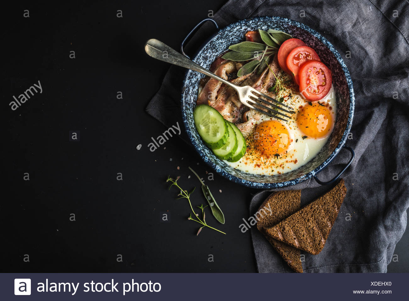 Breakfast set. Pan of fried eggs with bacon, fresh tomato, cucumber, sage and bread on dark serving board over black background, Stock Photo