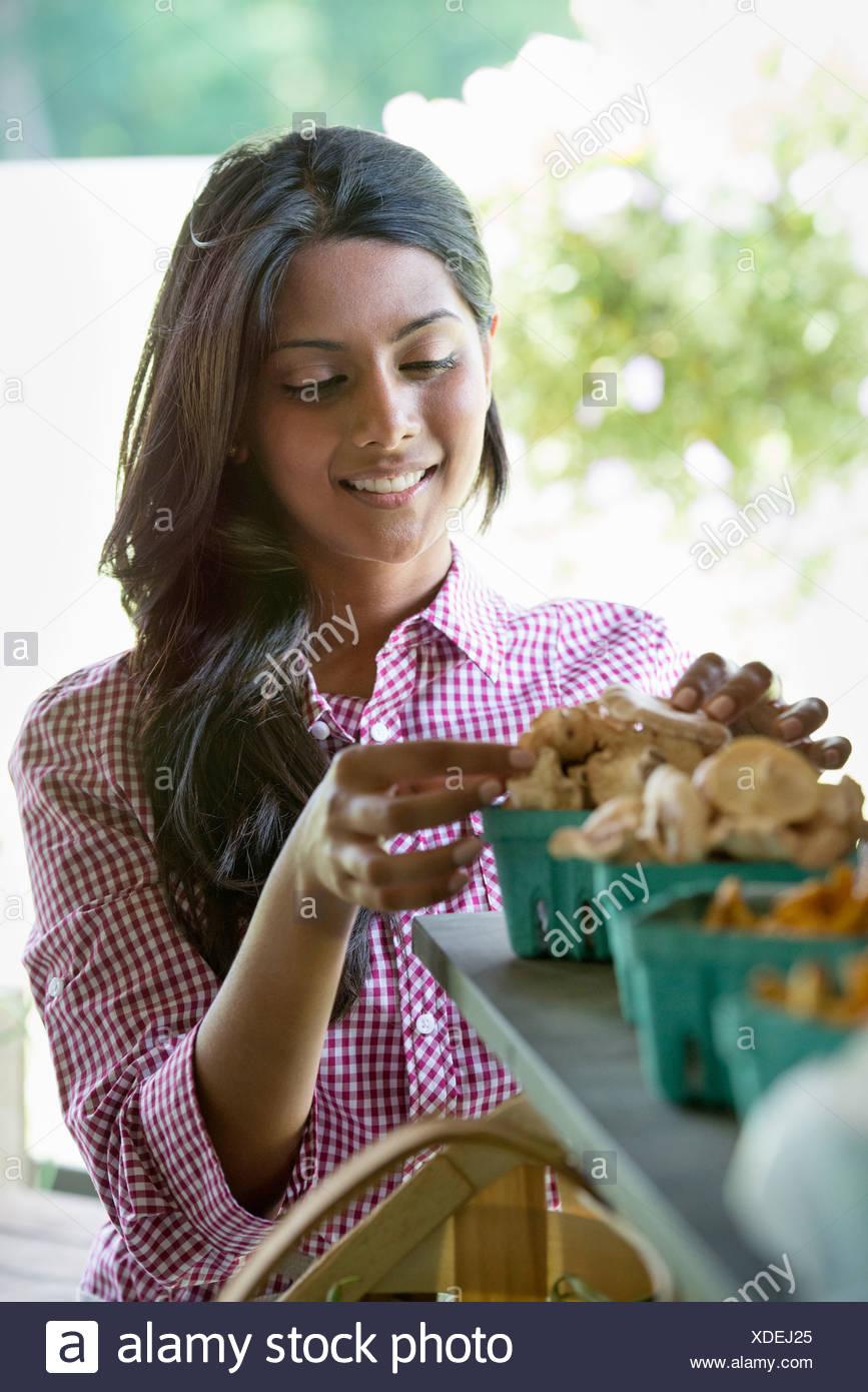 Farm stand organic vegetables. A woman sorting fresh mushrooms. - Stock Image