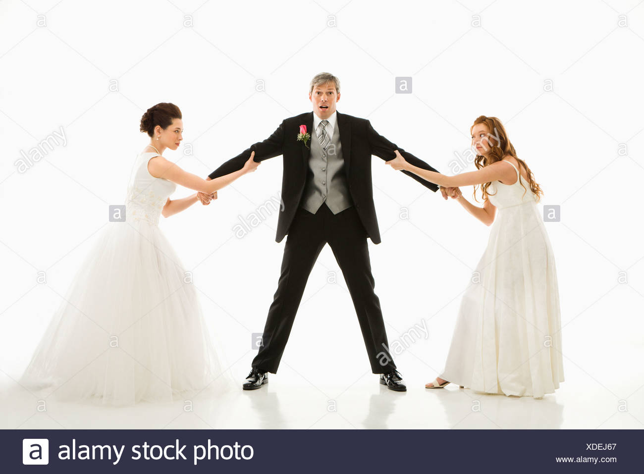 Caucasian and Asian brides pulling on Caucasian groom s arms