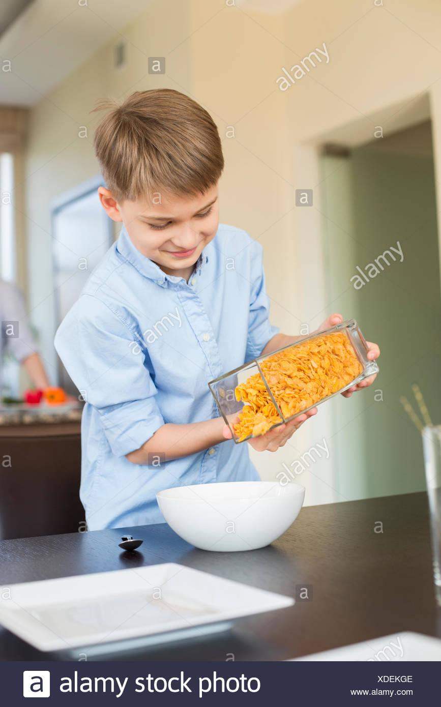 Smiling boy pouring corn flakes in bowl at home - Stock Image