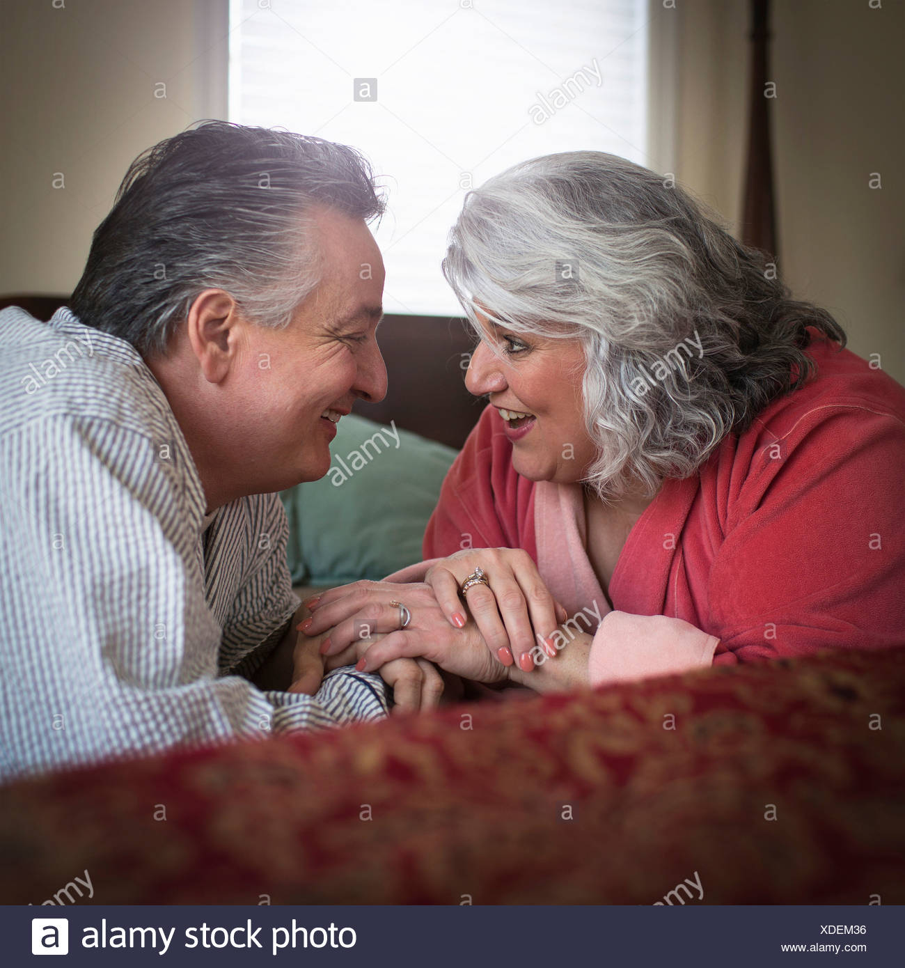 Affectionate mature adult couple lying on bed - Stock Image