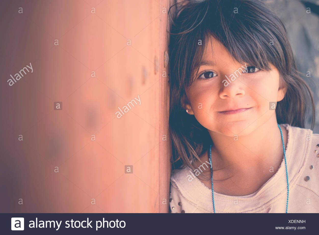Portrait of smiling girl leaning against wall - Stock Image