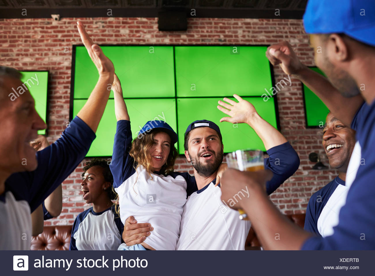 Friends Watching Game In Sports Bar On Screens Celebrating - Stock Image