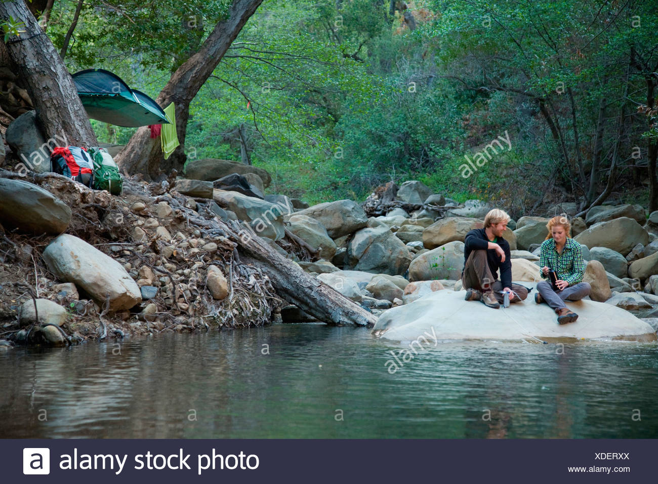 Backpackers taking a break at a river. - Stock Image