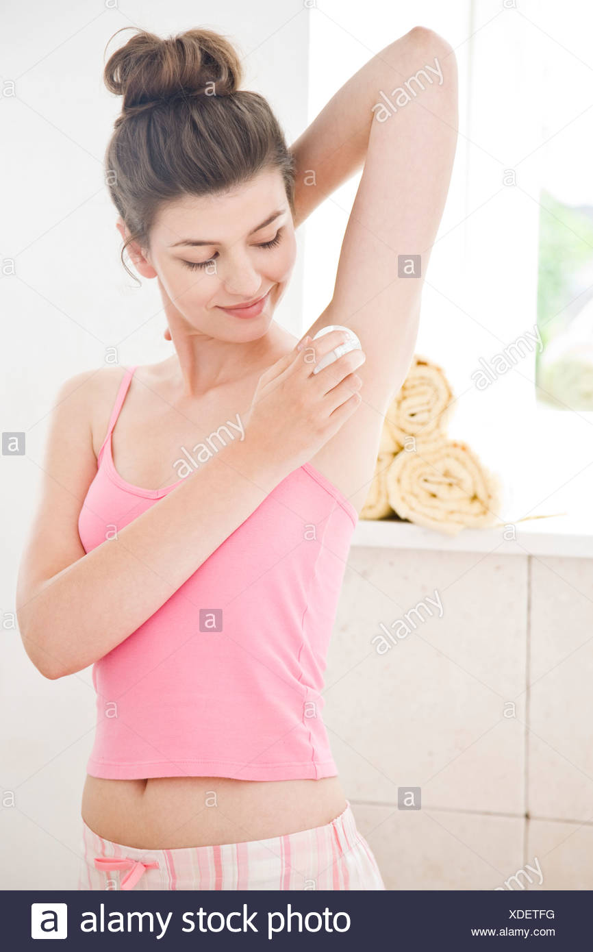woman applying deodorant - Stock Image