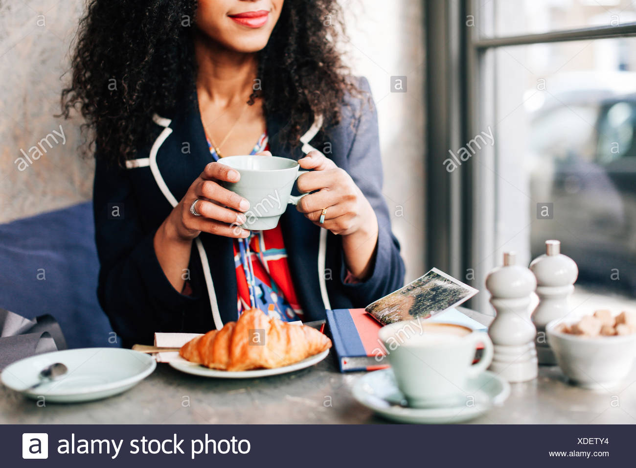 Cropped shot of woman holding coffee cup in cafe - Stock Image