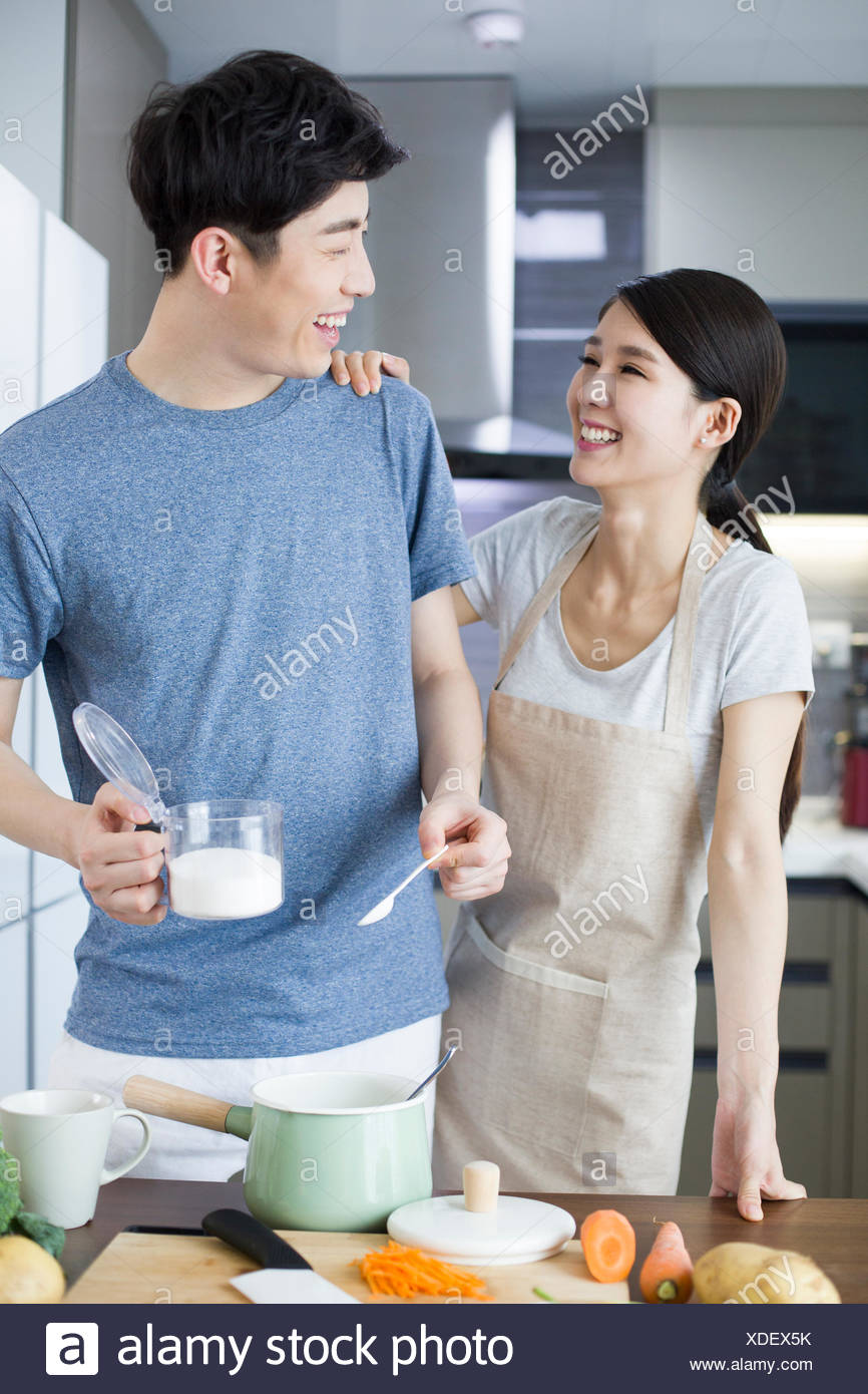 Happy young Chinese couple cooking in kitchen Stock Photo: 283684287 ...