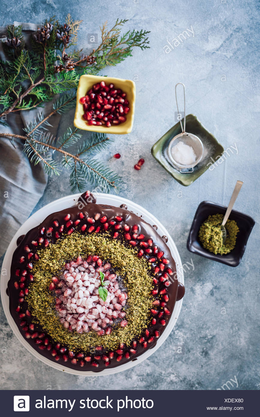 Christmas chocolate cake decorated with pomegranate seeds and pistachio accompanied by three small bowls and pine tree branches. Stock Photo