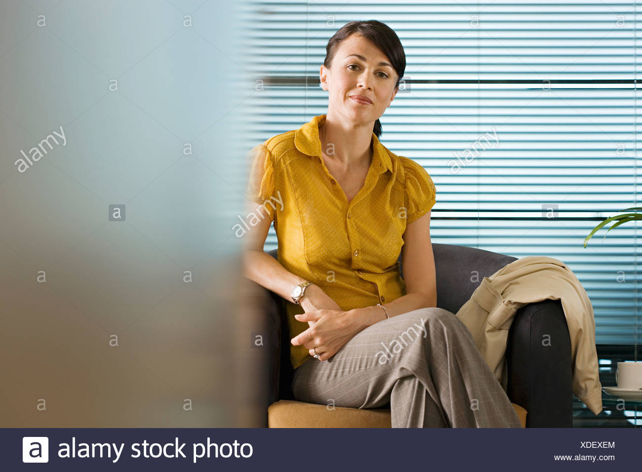Businesswoman in yellow short sleeved blouse sitting in office chair smiling portrait - Stock Image