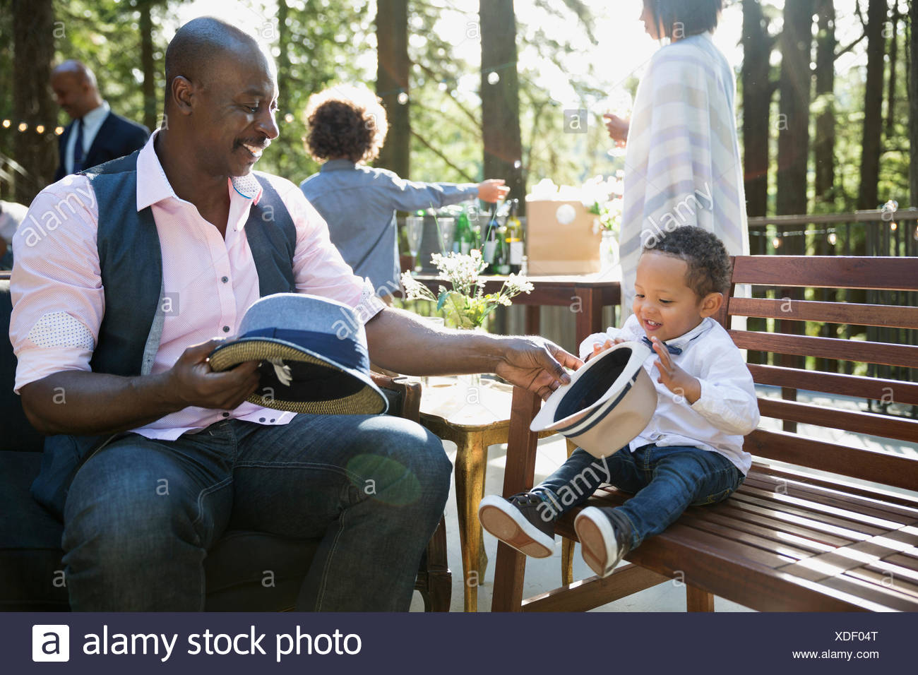 Father and son playing with hats at party on balcony - Stock Image