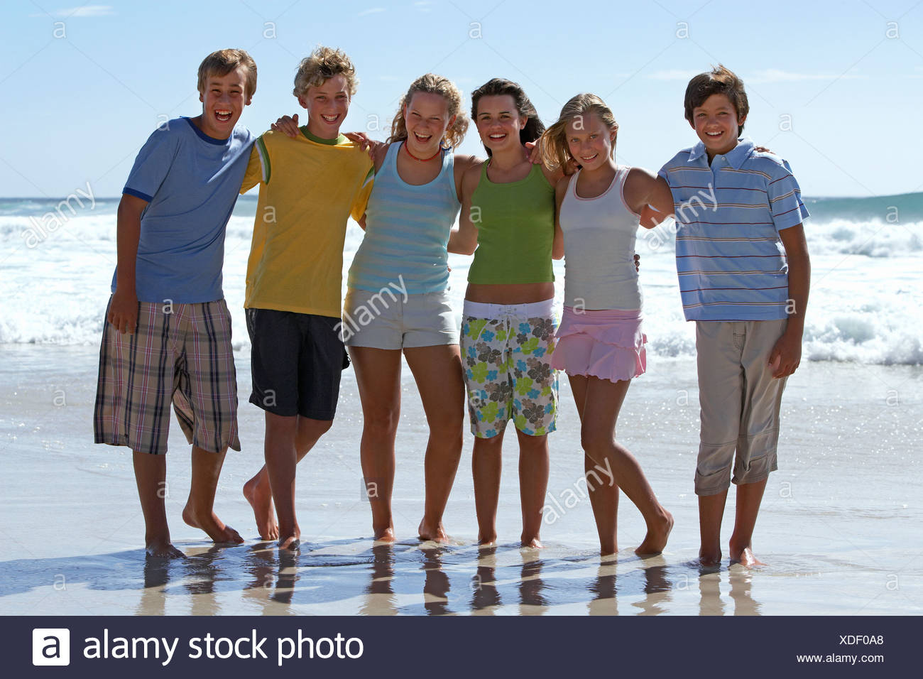 Group of teenagers 12 15 standing on sandy beach side by side smiling portrait - Stock Image