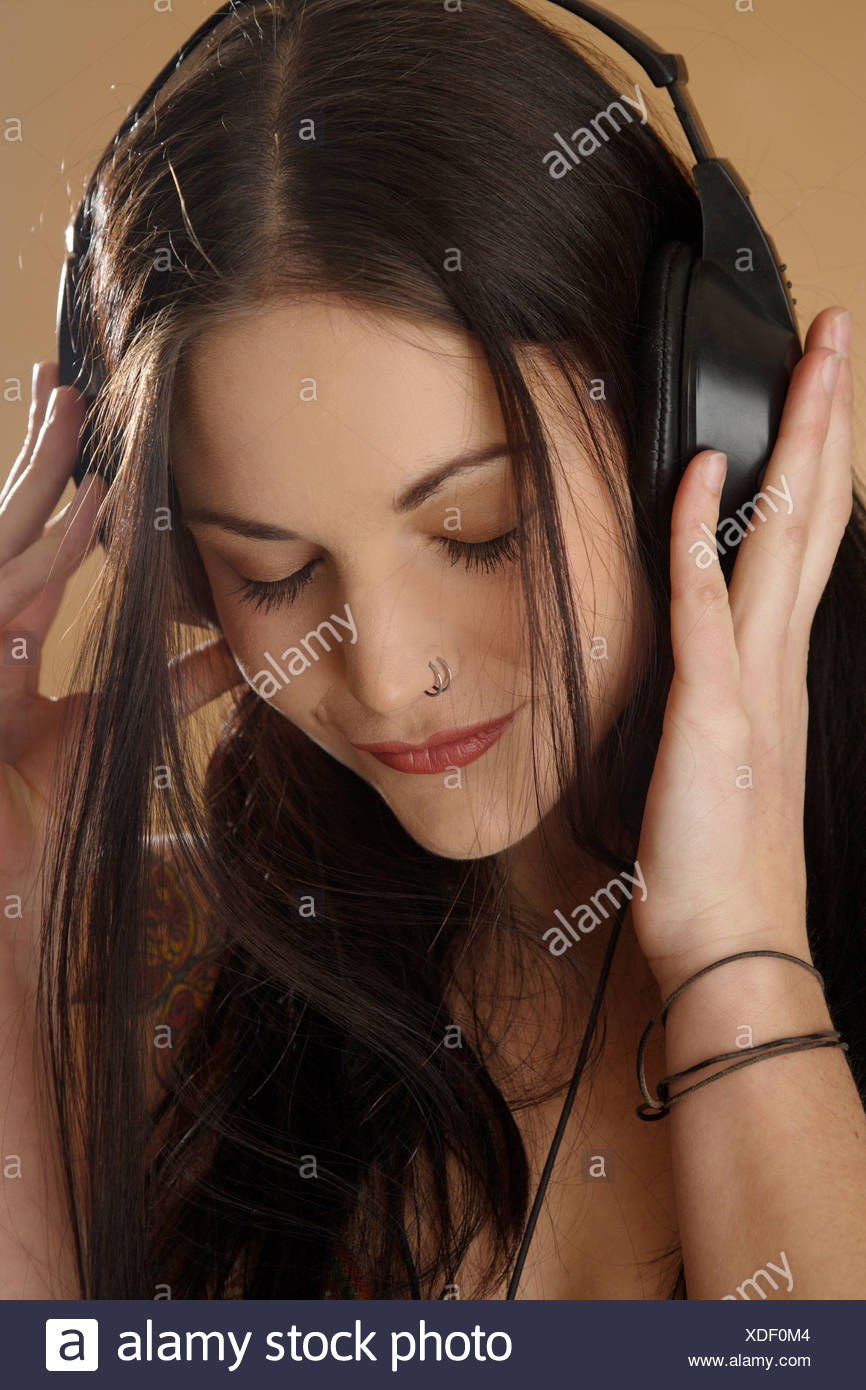 portrait of a young darkhaired woman with nose piercing and headphones on the head Stock Photo