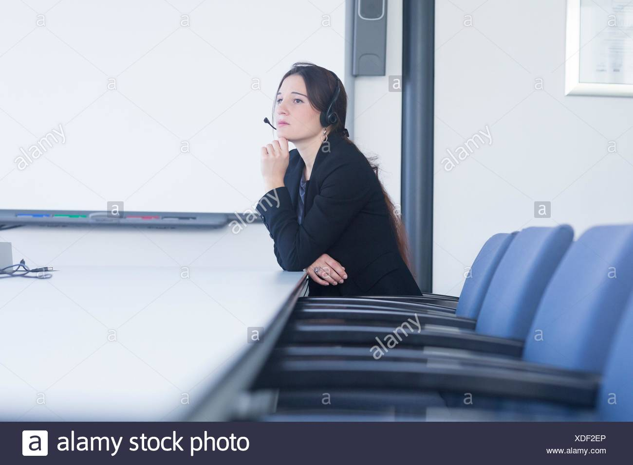 Telephonist contemplating in meeting room - Stock Image