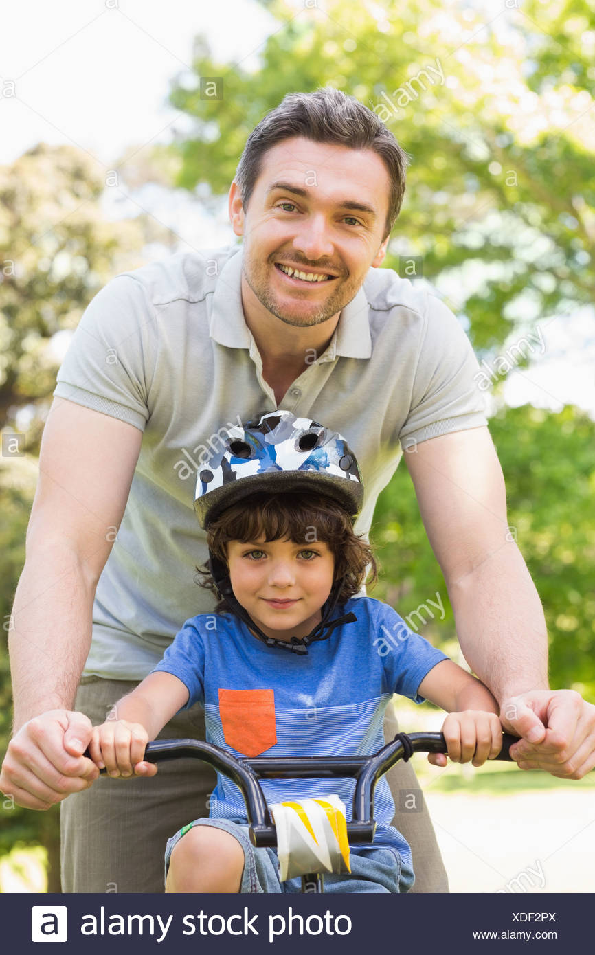 Man teaching his son to ride a bicycle - Stock Image