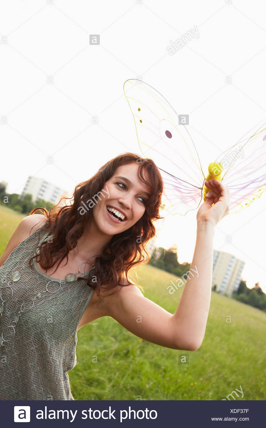 Woman holding toy butterfly close up - Stock Image