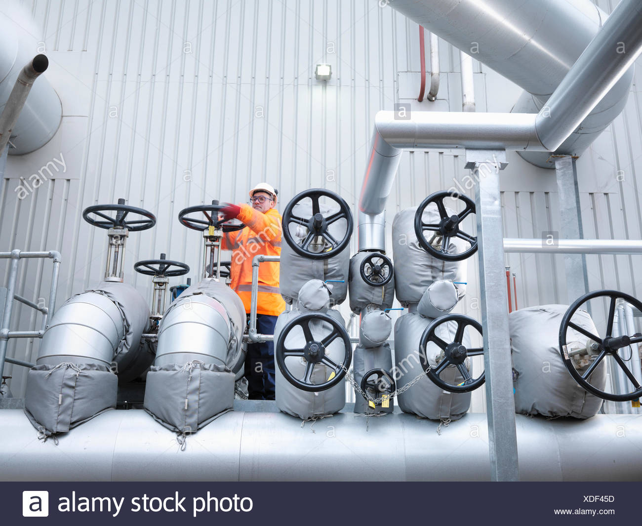 Worker turning valve of gas fired power station - Stock Image