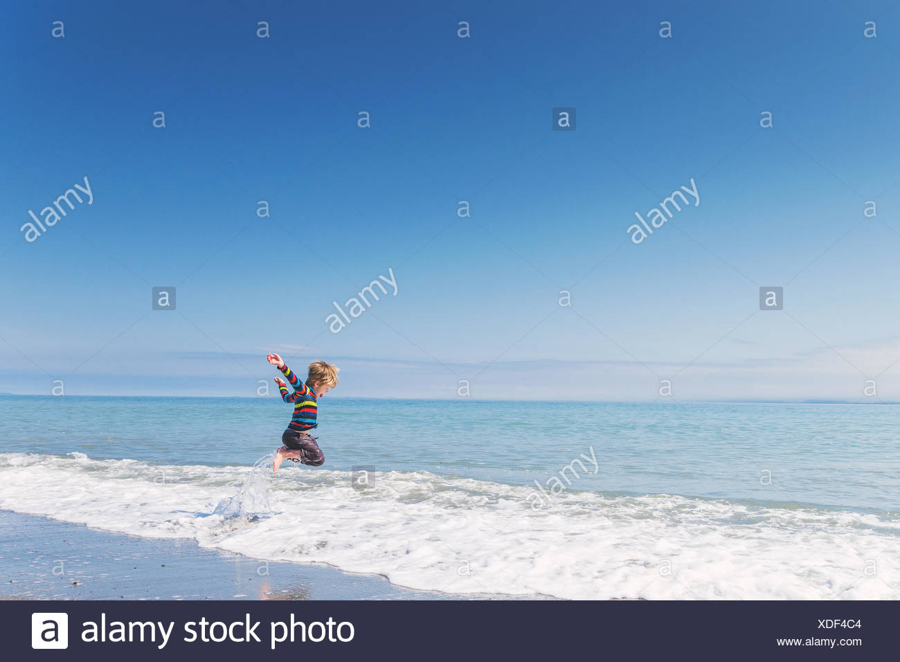 Boy jumping in surf - Stock Image