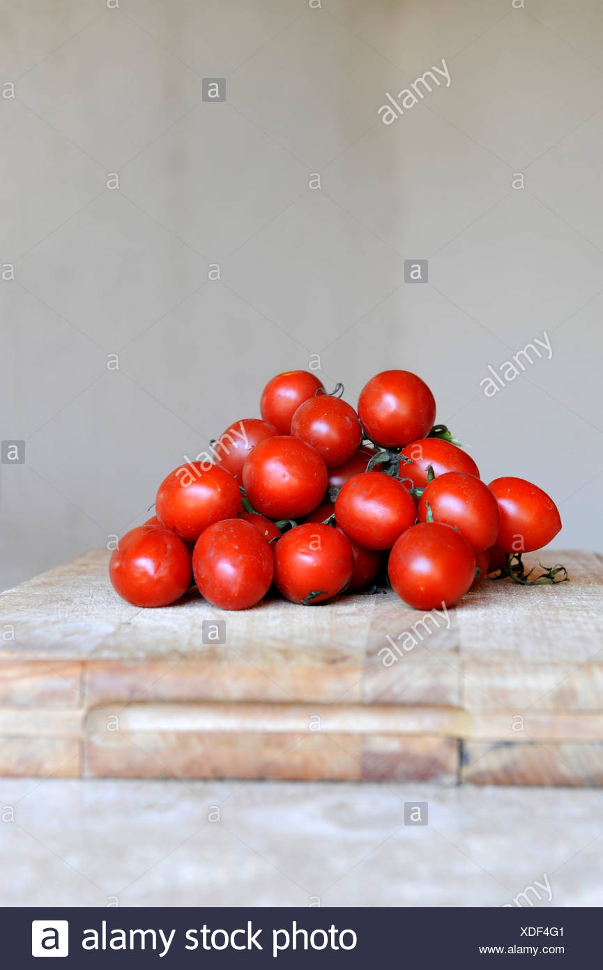 Ripe red Plum tomatoes on a chopping board - Stock Image