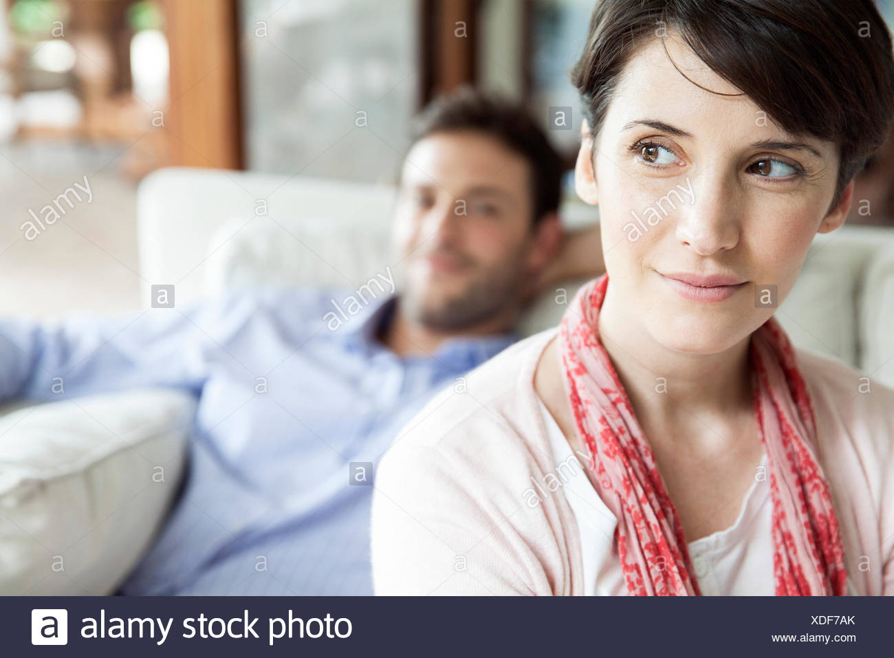 Woman looking away dreamily, man relaxing in background - Stock Image