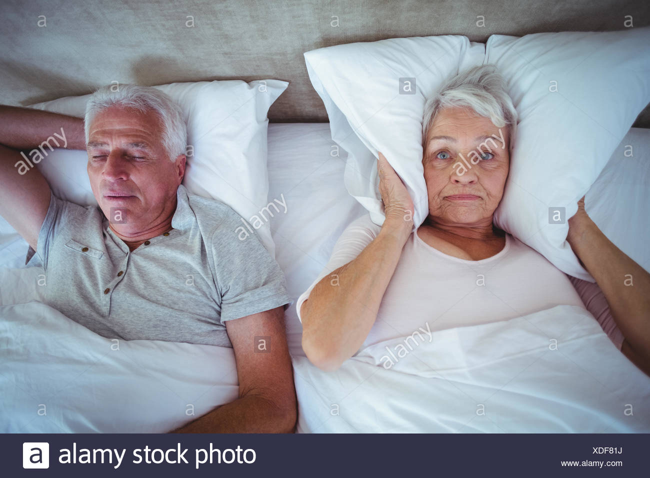 Wife blocking ears with pillow while husband snoring on bed Stock Photo