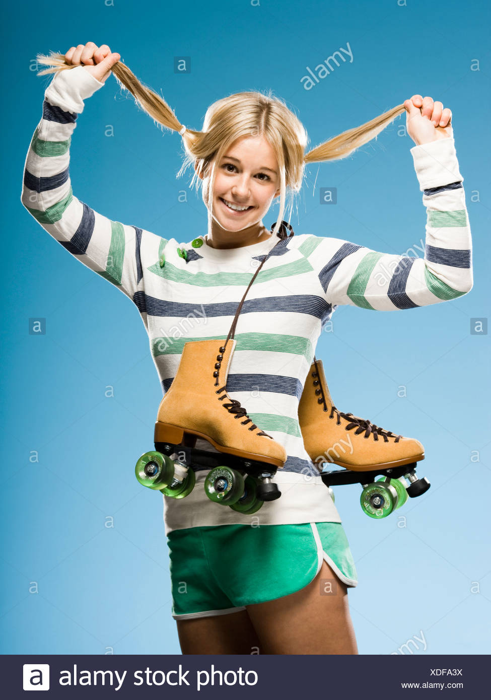 Studio portrait of young woman with roller skates - Stock Image