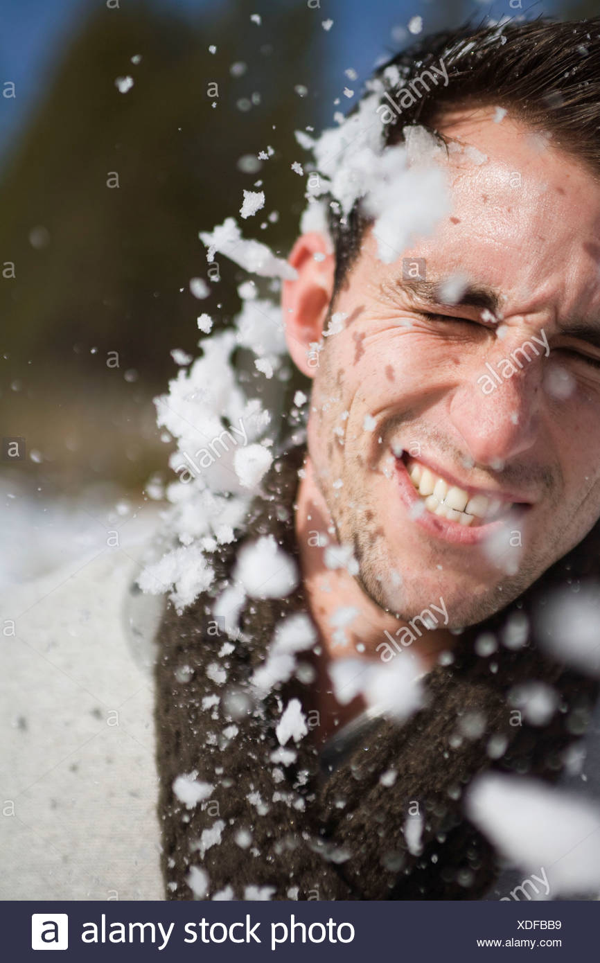 Man getting hit in face by snowball - Stock Image