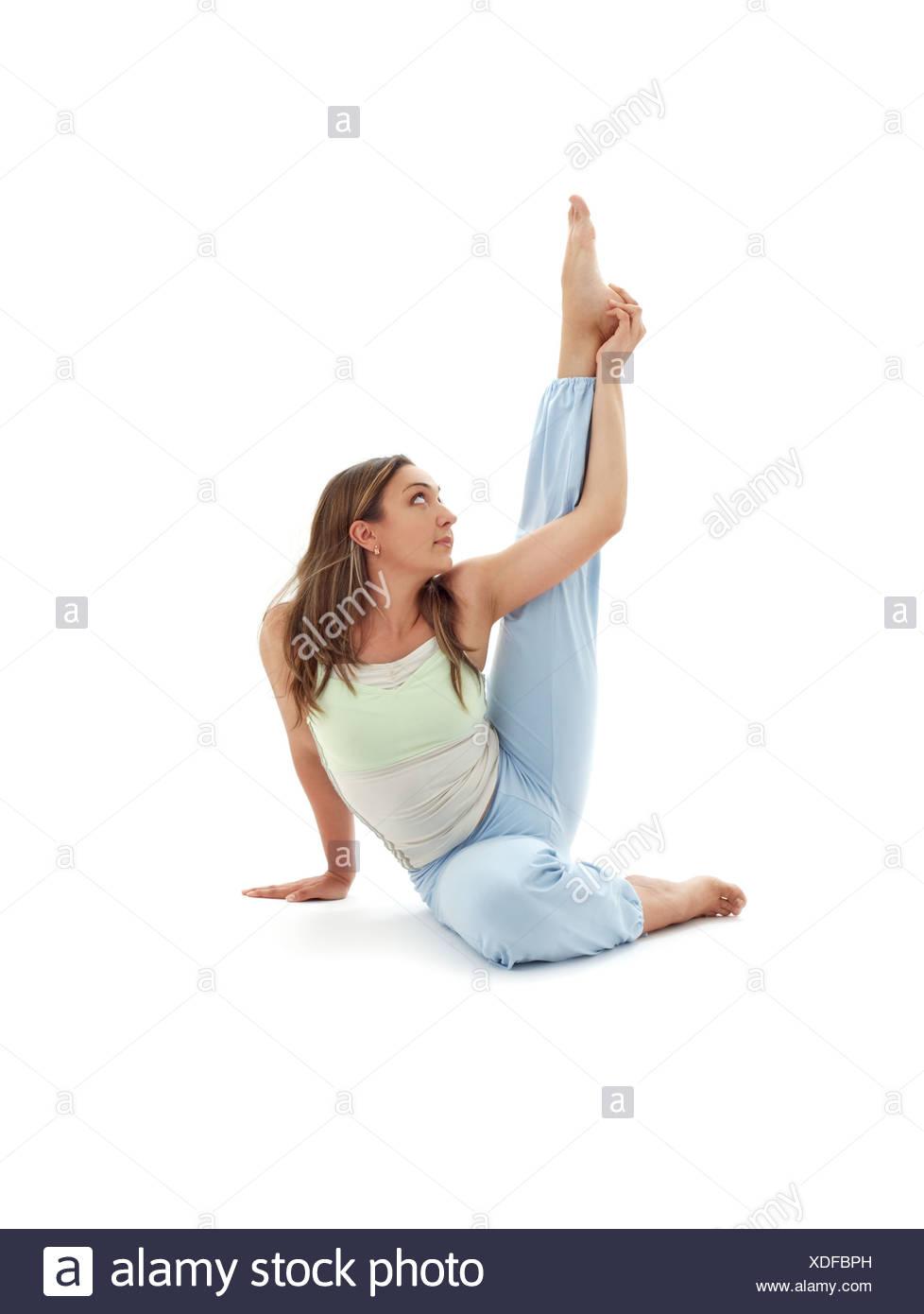 girl practicing krounchasana heron pose over white - Stock Image