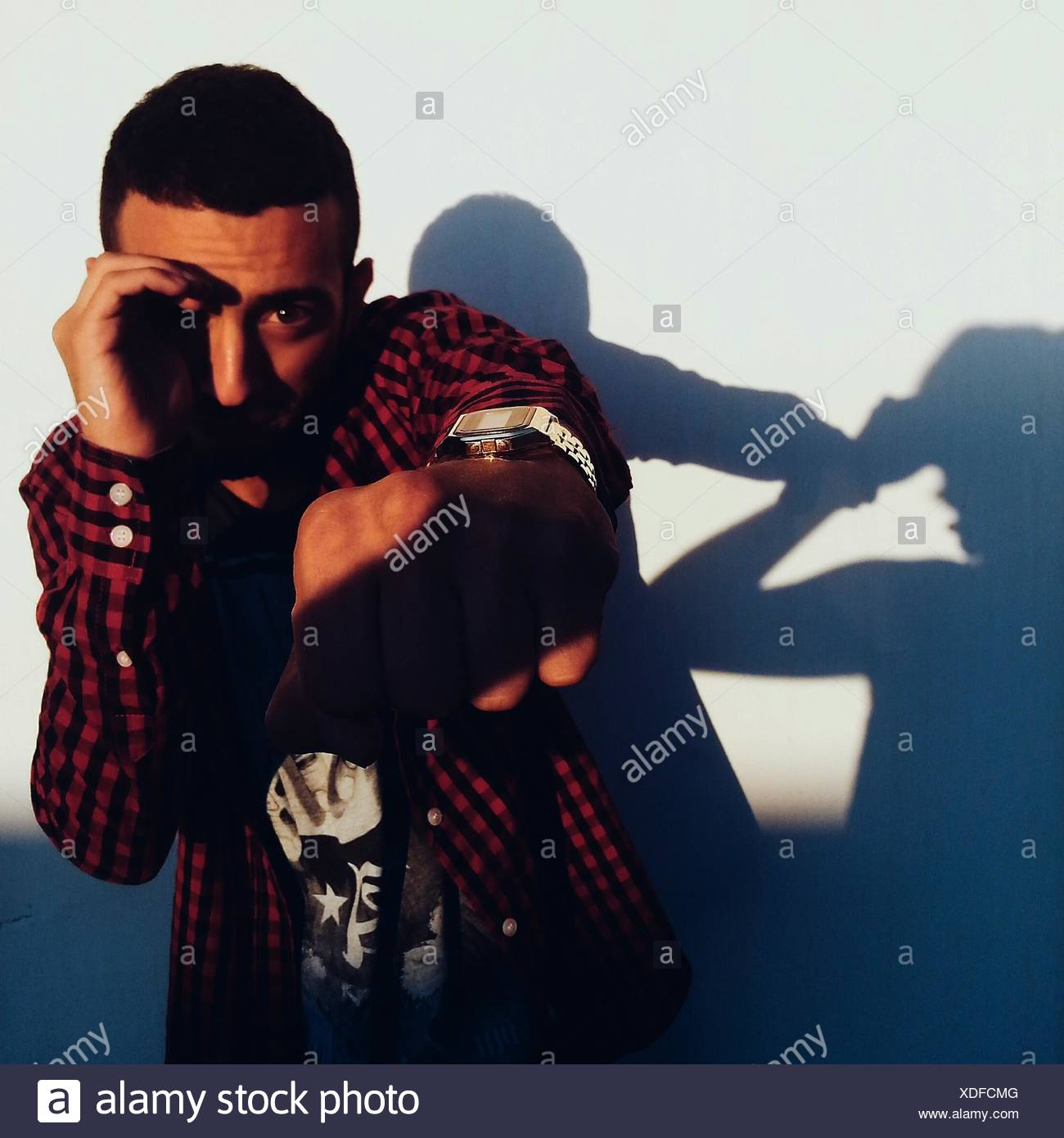 Portrait Of Young Man Punching Air Against Wall - Stock Image