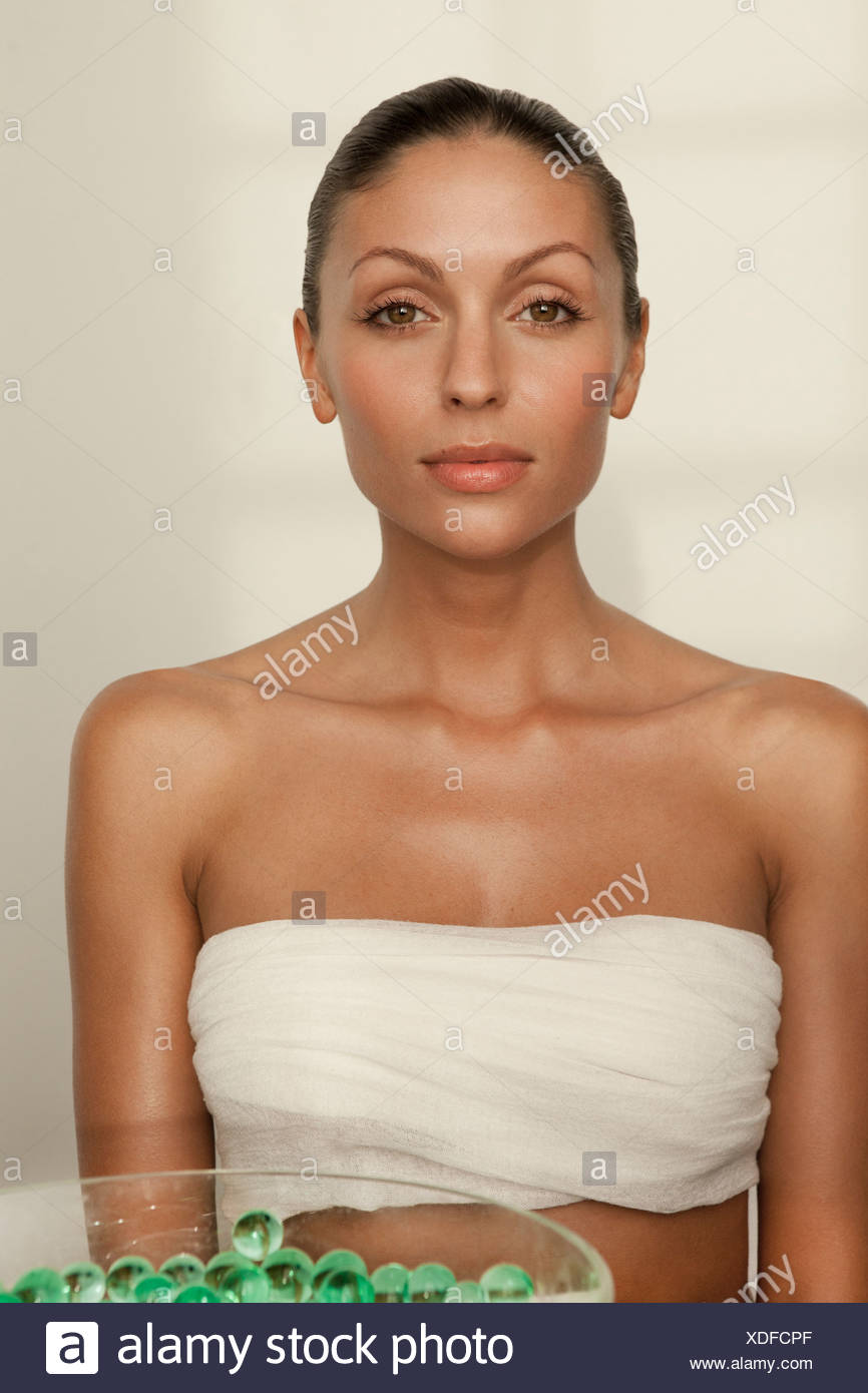 Woman sitting with bowl of glass beads - Stock Image