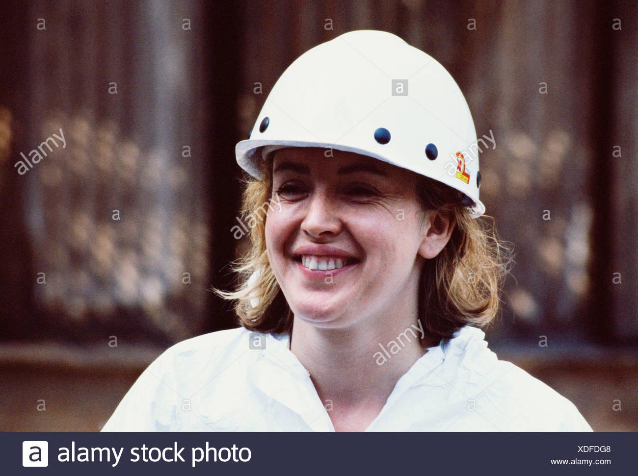 UK Industry. Woman wearing hard hat. - Stock Image