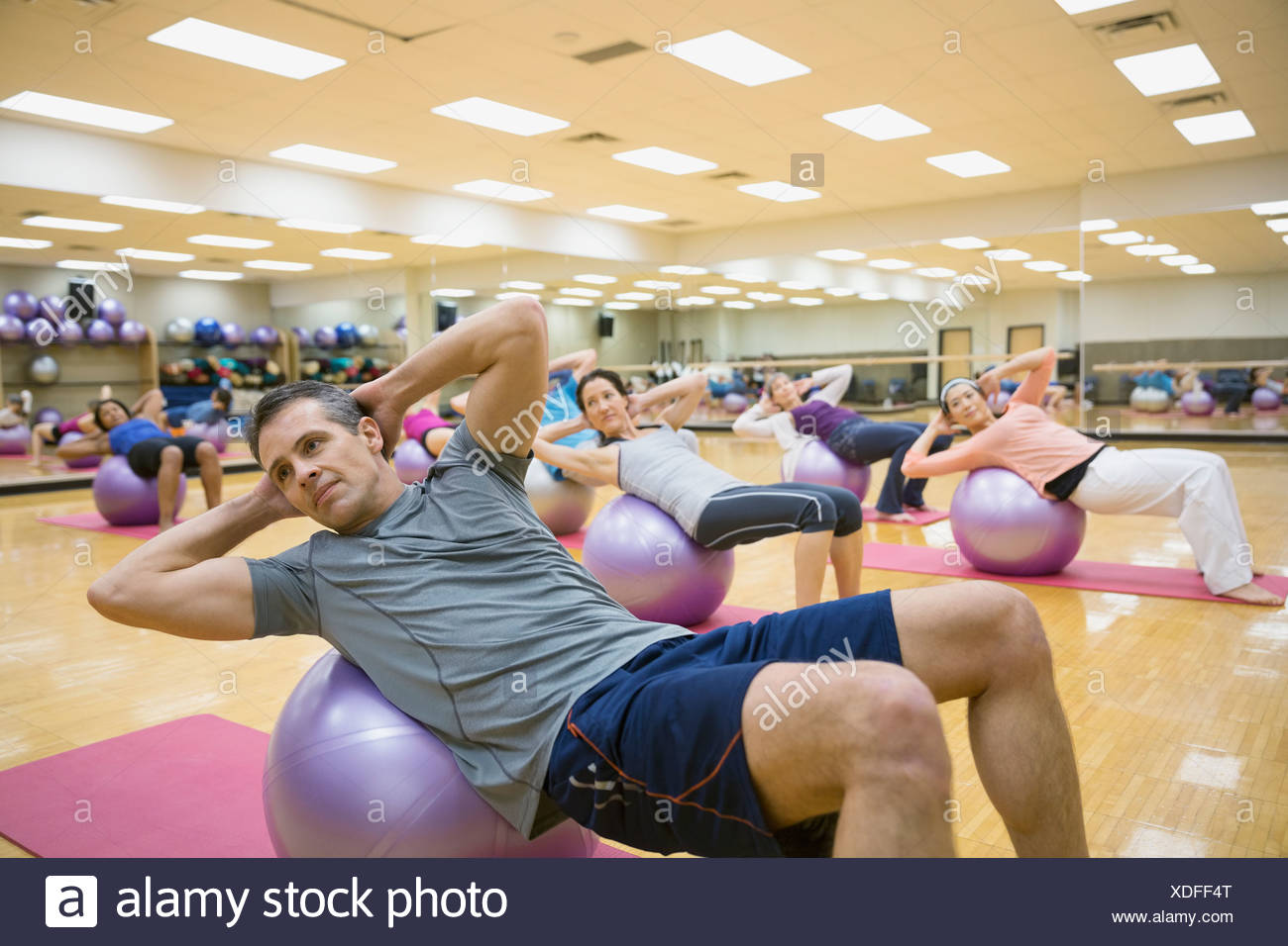 Group on fitness balls in exercise class - Stock Image