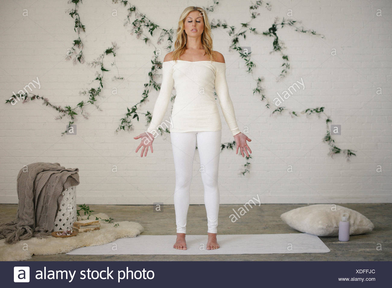 A blonde woman in a white leotard and leggings, standing on a white mat in a room. A creeper plant on the wall behind her. - Stock Image