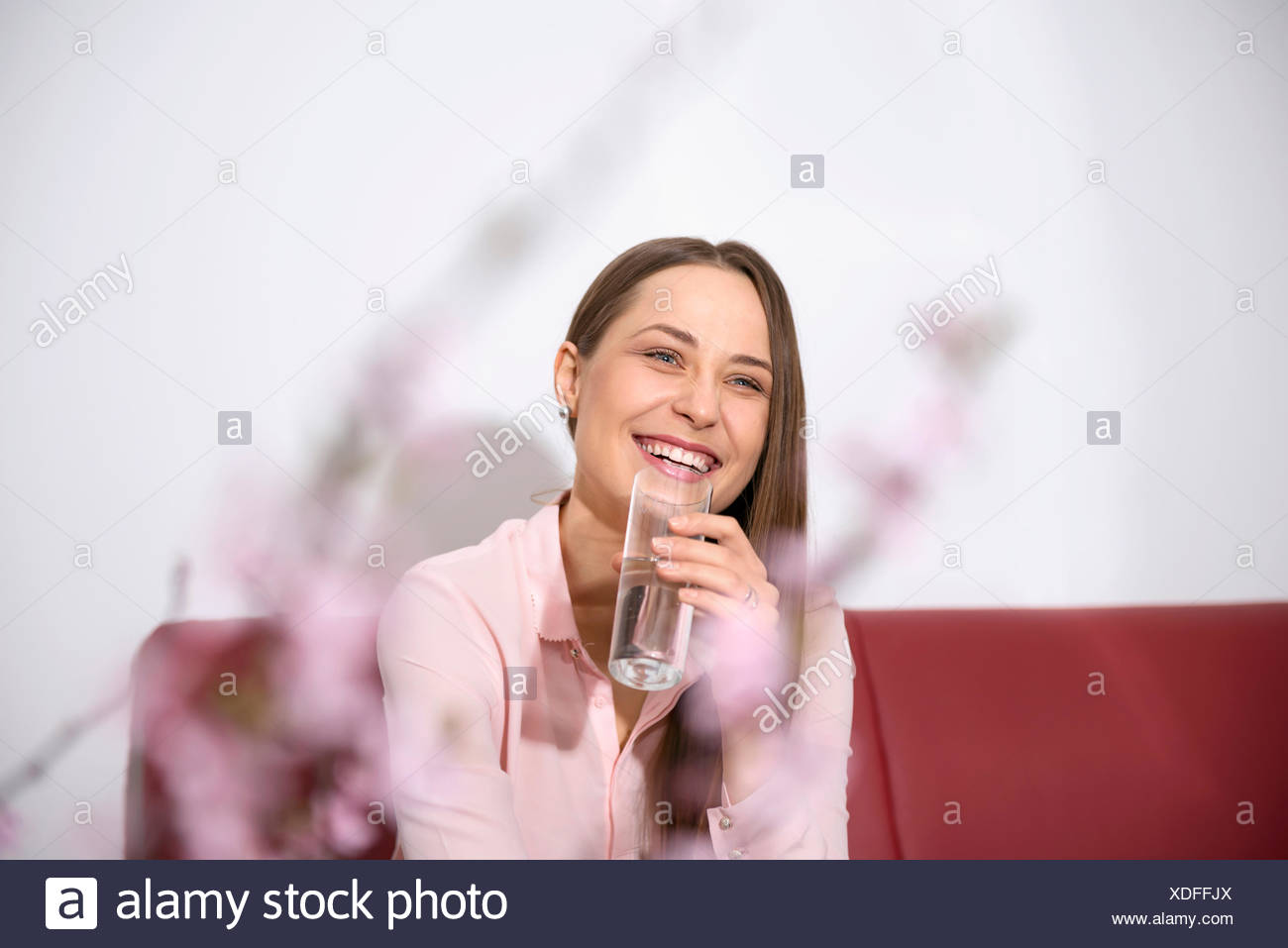 Young woman sofa sitting smiling drinking water - Stock Image