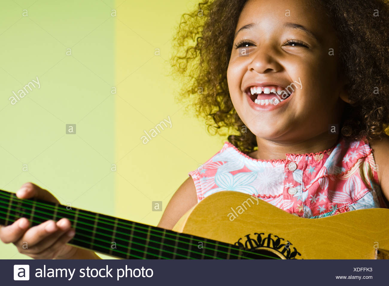 Little girl playing guitar - Stock Image