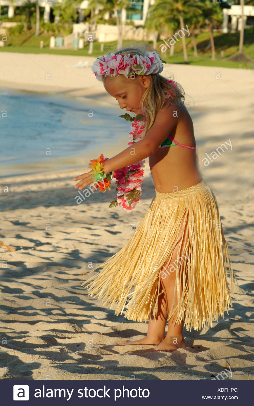 Young girl visiting the islands wearing a hula skirt and dancing on the beach - Stock Image