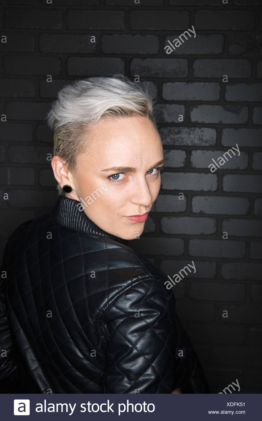 Portrait of serious blonde woman wearing leather jacket - Stock Image