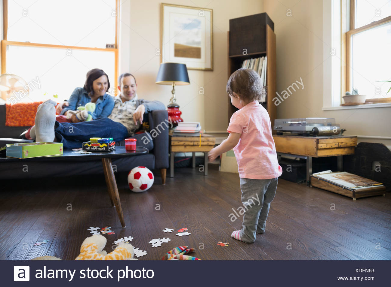 Parents watching baby daughter play with soccer ball Stock Photo
