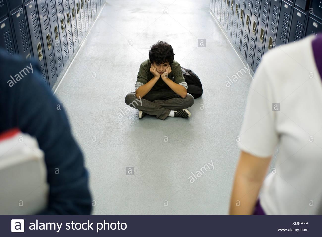 Teenage boy sitting sullenly on floor of school corridor, classmates in foreground - Stock Image