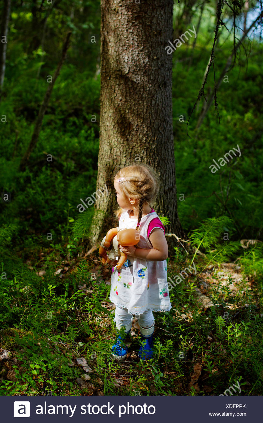 Finland, Paijat-Hame, Girl (2-3) with doll standing in front of tree - Stock Image