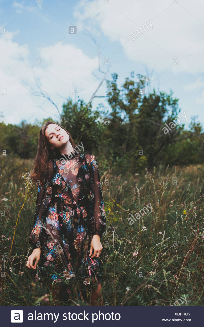 Portrait of a teenage girl standing in a meadow Stock Photo