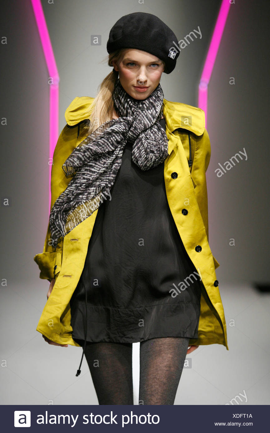 DKNY New York Ready to Wear Autumn Winter Model wearing black tunic mini dress tie string toggle hem, light mustard coat large - Stock Image