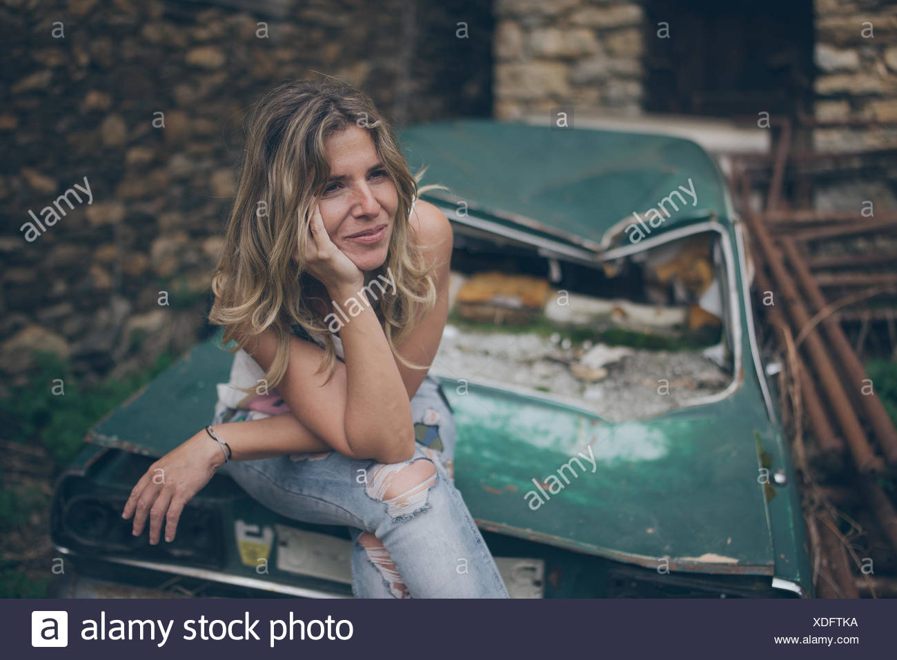 Young Woman Looking Away While Sitting On Abandoned Car - Stock Image