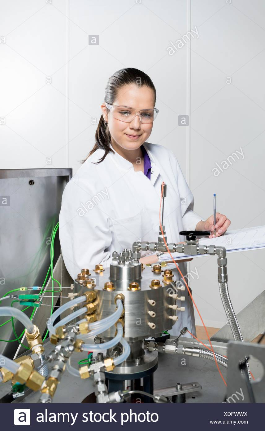 Portrait of female scientist, doing research on a innovative technology for mixing chemicals, at a hightech startup company Stock Photo