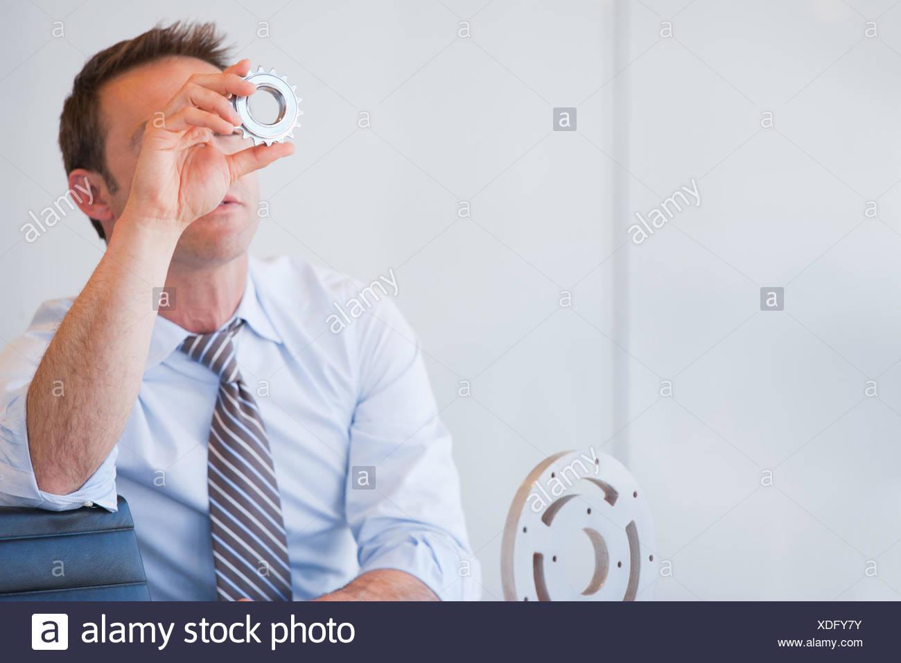 Businessman sitting at desk holding cog - Stock Image