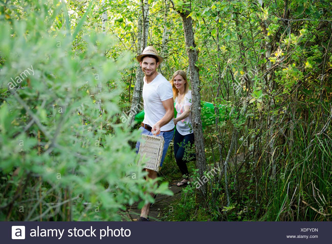 Mid adult couple walking through marshland with picnic basket - Stock Image
