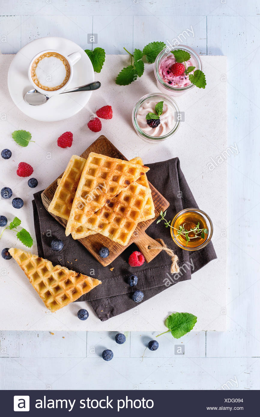 Breakfast theme with belgian waffles, berries, honey, cup of coffee and yogurt, served on wooden table with white background. Fl - Stock Image