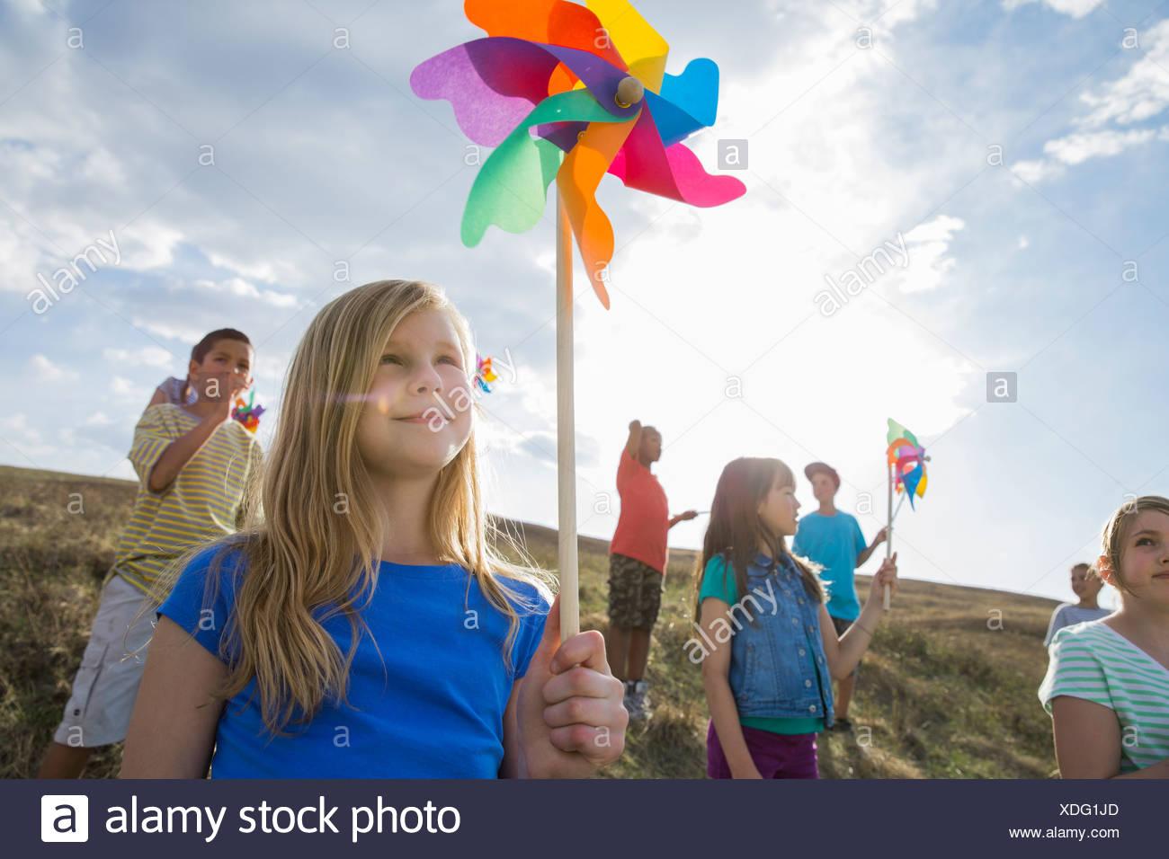 Smiling schoolchildren holding pinwheels outdoors - Stock Image